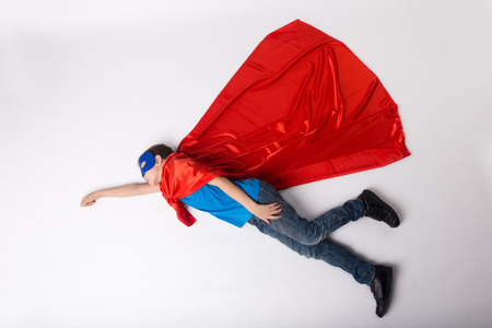 Superhero kid flying in superman costume. Super hero in red cape and blue mask