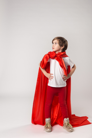 Female superhero kid posing in studio in superwoman costume