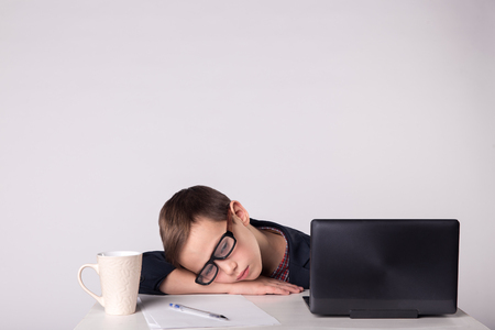 get tired: Young business boy get tired and fell asleep at the table