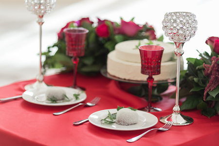 White cake, flowers, crystal glasses on the red wedding table Stock Photo