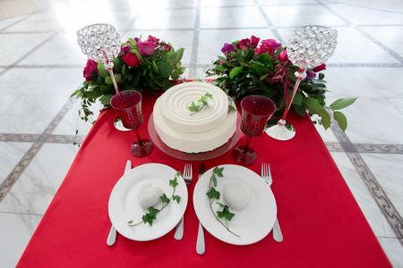 The decor of the wedding - wedding table for two. White cake, flowers, crystal glasses on the red table. view from above. Stock Photo