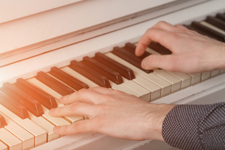 Mens hands on the keyboard of the piano with sunlight Stock Photo