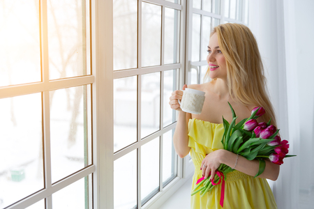 cup: Portrait of beautiful woman with tulip bouquet and cup tea. sunlight Stock Photo