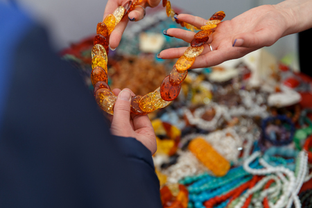 Woman shows beads on the market. Jewellery Made Of Amber. Stock Photo