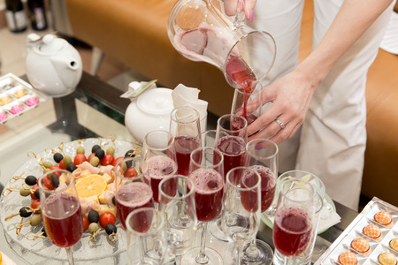 niños desayunando: glasses with juice. catering. girl is pouring juice. close up