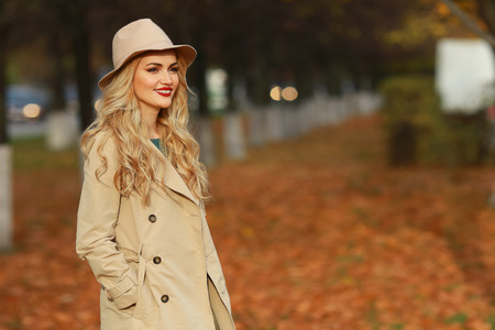 Beautiful elegant woman standing in fashionable beige hat in a park in autumn. free space.