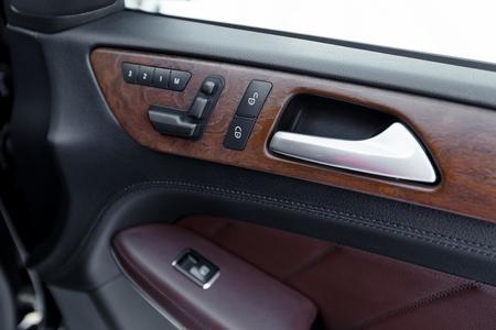 inwards: Door panel with power window controller. Detail of the car interior.