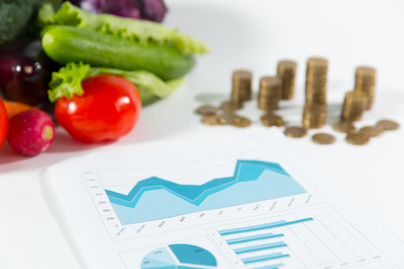 Lack of salary on vegetables, poverty concept. Healthy organic food composition against a stack of coins Stock Photo
