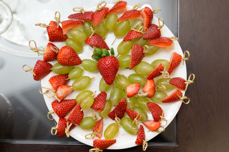 Snack from strawberry, grape. fruit catering served on a plate. top view