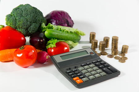 Lack of money on health food, poverty social status people concept. Fresh ripe vegetable composition against a stack of coins and calculator