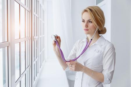 Doctor hermoso joven de la mujer que examina con el estetoscopio cerca de la ventana, luz del sol.