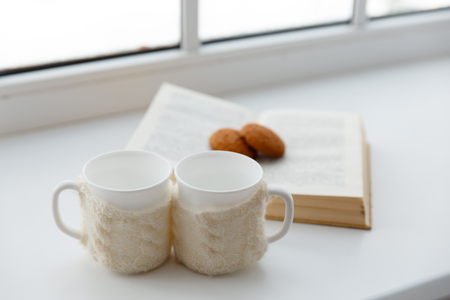 Two white mugs in a scarf stand on a table in the background of a window. selective focus. cozy atmosphere for coffee breaks
