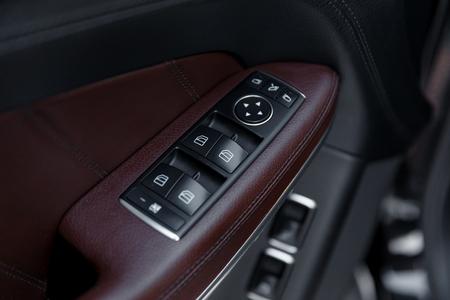 inwards: Door panel with power window controller. Detail of the car interior
