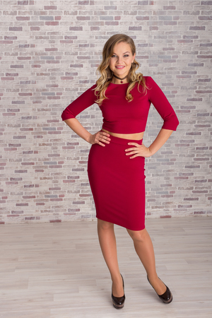 Beautiful young woman in full growth in red dress on a brick wall background. looking at camera. Stock Photo