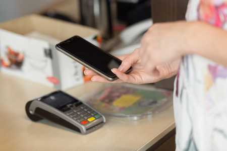 lady on phone: Woman paying bill through smartphone using nfc technology in cafe. Stock Photo