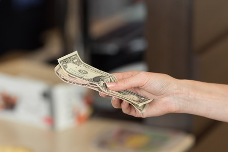 Woman pays cash for the breakfast in the cafe. close-up.