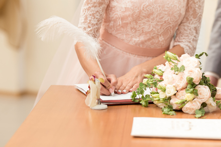 Bride and bridegroom signing the marriage contract after the wedding ceremony. Stock Photo