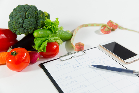 Vegetables, measuring tape, mobile phone and notebook with diet plan isolated on white background, top view. Nutritionist doctor workspace concept Stock Photo