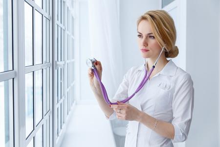 Joven hermosa doctora examinando con estetoscopio junto a la ventana. Foto de archivo