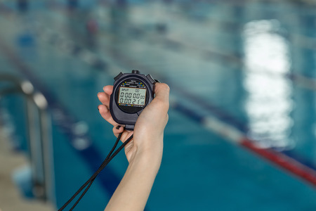 Close-up of coach hand holding stopwatch at poolside.