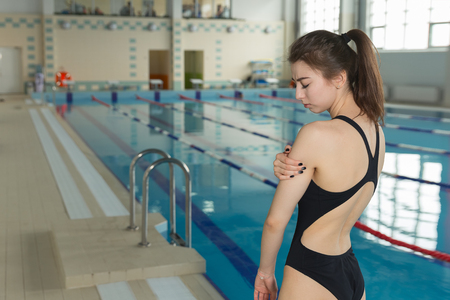swimmer sportsman with shoulder pain before swimming moment standing near poolside. sport injury concept Imagens - 80179825
