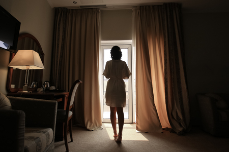 Beautiful young woman, silk bathrobe, standing by the window, natural light, toned Standard-Bild