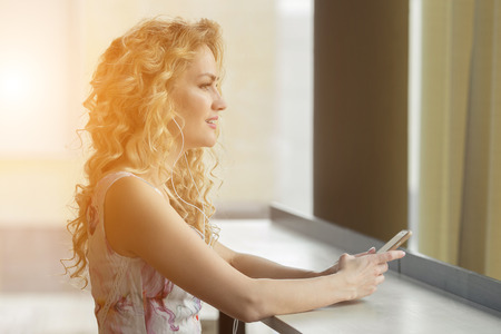 earbud: Beautiful young female is listening music by her smartphone at cafe in sunlight Stock Photo