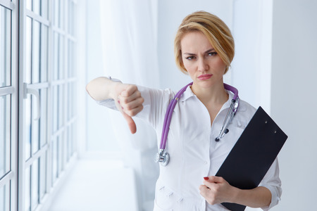 alternative practitioner: Closeup portrait, doctor woman, giving thumbs down gesture looking with negative expression, disapproval. Unhappy female health care professional. Emotion facial expression.