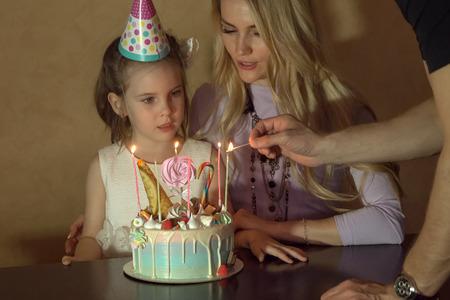 Moeder en dochter tellen kaarsen op een verjaardagstaart. Klein meisje in een feestelijke hoed op een kinderfeestje.