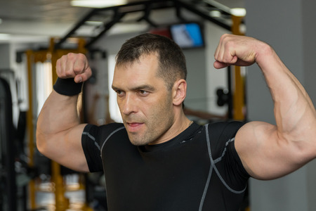 Young muscular man flexing his biceps in gym. Stock Photo