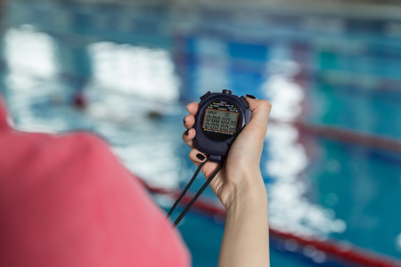 Swimming coach holding stopwatch poolside at the leisure center