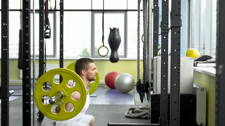heavy: Young muscular man exercising in the gym. Crossfit training. side view.