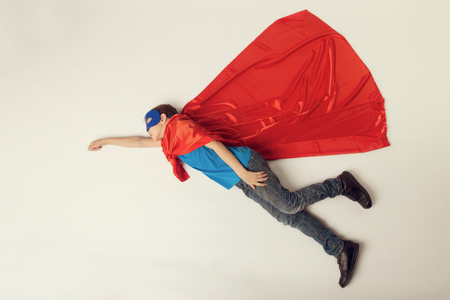 Superhero kid flying. Super hero boy in red cape and blue mask. copyspace, toned.