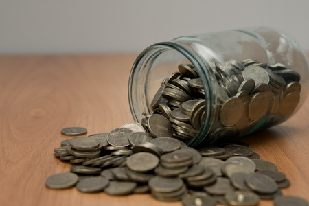 Overturned glass jar full of coins, money box. Cash savings concept. Penny collecting