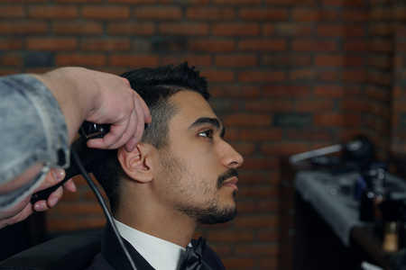 hairdresser: The hands of young barber making haircut to attractive man in barbershop.