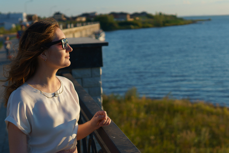 Young girl in eyeglasses enjoys the sunset on the waterfront. copyspace