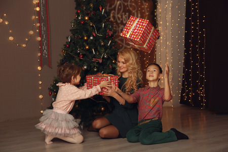 Mother and children exchanging and opening Christmas presents.