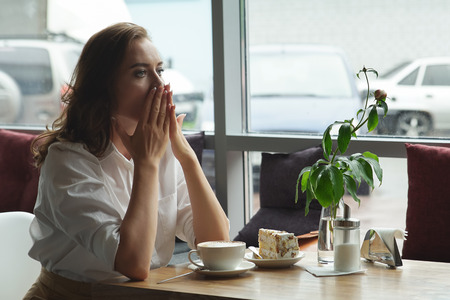 pain: Beautiful sad female sitting alone at the cafe. Sad young woman deep in cafe. She is sad.