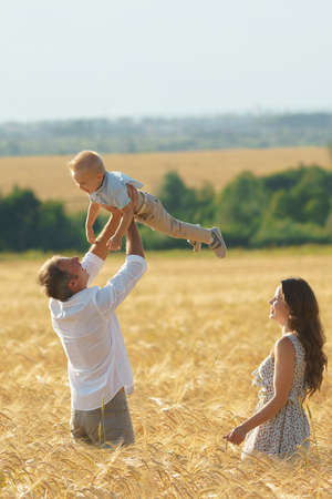Parents happiness, father playing with son on the wheat field. Family walking with child outdoor Stock Photo