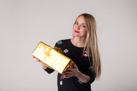 Smiling beautiful woman with gift box in golden wrapping paper, ribbon and bow.
