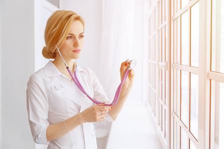 hospital patient: Young beautiful female doctor examining with stethoscope near window.
