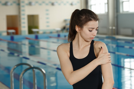 swimmer sportsman with shoulder pain before swimming moment standing near poolside. sport injury concept