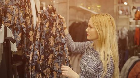 Close-up of a girl choosing a dress in a department store, sunlight