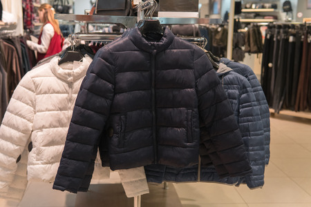 Row of white, black and gray down coats on the rack, clothing shop interior on background. Warm winter wear in fashion store Archivio Fotografico