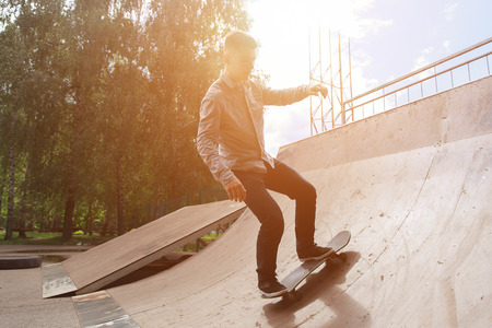 Active rest in the skate park. ute guy hipster in shirt and jeans is riding skateboard slide in the park against backdrop of trees and bright, sunlight