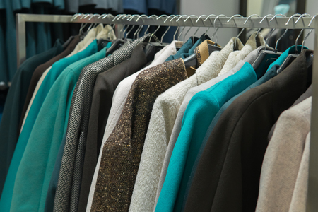 warm winter and autumn colourful wear in fashion store hanging on rack, shopping.