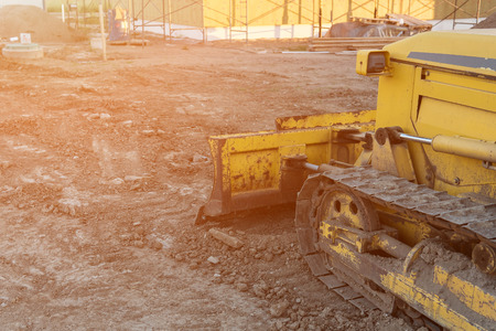 close up of yellow bulldozer during construction work on a private house, sunlight. copyspace