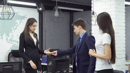 Big deal . Young male businessman in formal clothes gives bundle of banknotes to young woman - boss of large firm next to his assistant while working at the office
