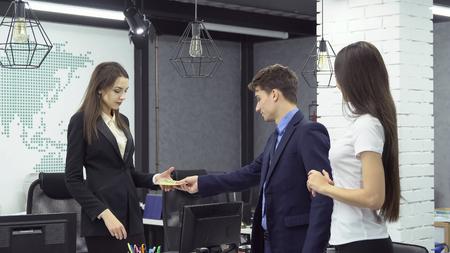 Grosse affaire . Jeune homme d'affaires en vêtements formels donne un paquet de billets à une jeune femme - patron d'une grande entreprise à côté de son assistant tout en travaillant au bureau