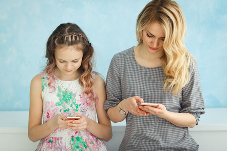 Mother and daughter are sitting next to each other looking in their phones and do not talk.